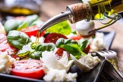 De salade van Caprese Mediterrane Salade De tomatenbasilicum van de mozarellakers en olijfolie op oude eiken lijst Italiaanse keu Royalty-vrije Stock Afbeeldingen