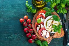 De salade van Caprese Mozarellakaas, tomaten en de bladeren van het basilicumkruid stock afbeelding