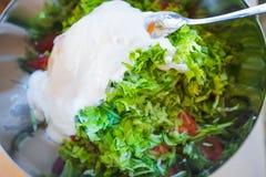 de salade van komkommer, de gesneden salade, de tomaat en de yoghurt in ijzer werpen Stock Afbeelding