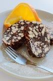 De salami van het koekje met sinaasappel en vork royalty-vrije stock afbeeldingen