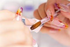 De salon van de schoonheid: Manicure, die op spijker schildert Stock Afbeeldingen