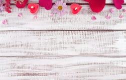 De samenstelling met kaarsen, de bloemen en de harten op witte plattelander streven na Stock Fotografie