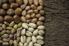 De samenstelling met noten, de hazelnoten en de pistaches sluiten omhoog Royalty-vrije Stock Afbeeldingen