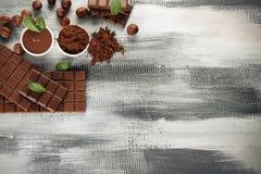 De samenstelling met smakelijke chocolade en de cacao poederen zich op houten lijst, hoogste mening royalty-vrije stock afbeeldingen
