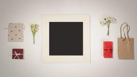 De samenstelling met zwart fotokader, de rode giftdozen, de ambachtzak, de canvaszak met rode hartvormen en het de lentegebied bl stock foto's