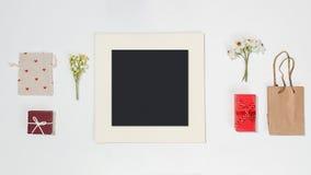 De samenstelling met zwart fotokader, de rode giftdozen, de ambachtzak, de canvaszak met rode hartvormen en het de lentegebied bl royalty-vrije stock afbeeldingen