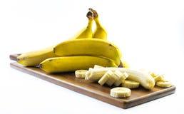 De samenstelling van bananen één van hen wordt gepeld en besnoeiing op een houten raad en een witte achtergrond - zijaanzicht Stock Foto's
