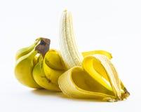 De samenstelling van bananen één van hen wordt gepeld op een witte achtergrond Stock Foto's