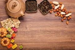 De samenstelling van de thee op een houten oppervlakte bruine theepot van klei met zich het verspreiden van thee, amandel en haze Stock Fotografie