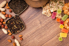 De samenstelling van de thee op een houten oppervlakte bruine theepot van klei met zich het verspreiden van thee, amandel en haze Royalty-vrije Stock Afbeeldingen