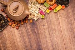 De samenstelling van de thee op een houten oppervlakte bruine theepot van klei met zich het verspreiden van thee, amandel en haze Royalty-vrije Stock Foto