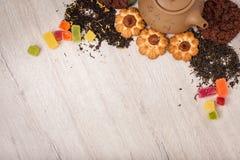 De samenstelling van de thee op een houten oppervlakte bruine theepot van klei met zich het verspreiden van thee, amandel en haze Stock Foto's