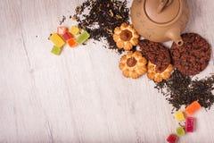 De samenstelling van de thee op een houten oppervlakte bruine theepot van klei met zich het verspreiden van thee, amandel en haze Stock Afbeeldingen