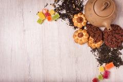 De samenstelling van de thee op een houten oppervlakte bruine theepot van klei met zich het verspreiden van thee, amandel en haze Stock Afbeelding