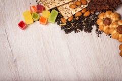 De samenstelling van de thee op een houten oppervlakte het verspreiden zich van thee, amandel en hazelnoot Groene, zwarte thee Ko Stock Foto