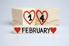 De samenstelling van de Valentine'sdag met houten kalender De met de hand geschreven 14de, rode harten van Februari Stock Fotografie
