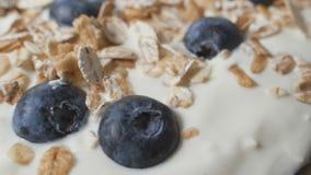 De samenstelling van een typisch echt ontbijt maakte met yoghurt, bosbessen, muesli stock videobeelden