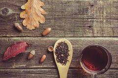 De samenstelling van de herfst De vaas met droog doorbladert, appel en kaarsen bij het ontslaan Kop thee, de herfstbladeren en he stock fotografie