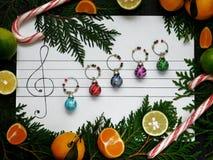 De samenstelling van Kerstmis De ballen van de Kerstmisdecoratie worden geschikt op het document zoals muzieknota's Royalty-vrije Stock Foto