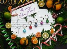 De samenstelling van Kerstmis De ballen van de Kerstmisdecoratie worden geschikt op het document zoals muzieknota's Royalty-vrije Stock Foto's