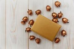 De samenstelling van Kerstmis Gouden huidige doos en gouden eikels Witte Houten lijst Royalty-vrije Stock Foto's
