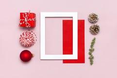 De samenstelling van Kerstmis Het witte fotokader, rode envelop, spar vertakt zich, kegels, bal, streng, gift, houten speelgoed o stock fotografie