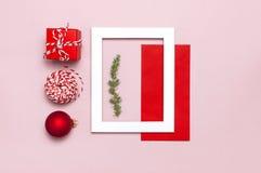 De samenstelling van Kerstmis Het witte fotokader, rode envelop, spar vertakt zich, kegels, bal, streng, gift, houten speelgoed o royalty-vrije stock fotografie