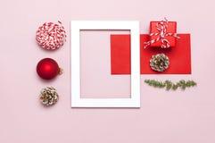 De samenstelling van Kerstmis Het witte fotokader, rode envelop, spar vertakt zich, kegels, bal, streng, gift, houten speelgoed o stock foto's