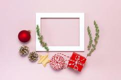De samenstelling van Kerstmis Het witte fotokader, spartakken, kegels, rode bal, streng, gift, houten speelgoed op roze Vlakte al royalty-vrije stock fotografie