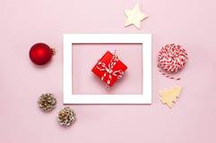De samenstelling van Kerstmis Het witte fotokader, spartakken, kegels, rode bal, streng, gift, houten speelgoed op roze Vlakte al royalty-vrije stock foto