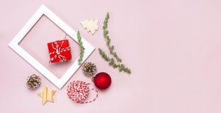 De samenstelling van Kerstmis Het witte fotokader, spartakken, kegels, rode bal, streng, gift, houten speelgoed op roze Vlakte al stock afbeelding