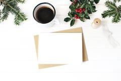 De samenstelling van Kerstmis De kop van koffie, hulstbessen, sparkerstboom vertakt zich en zijdelint op witte houten lijst stock foto's