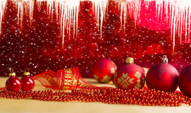 De samenstelling van Kerstmis Rode Snuisterijen op Vakantieachtergrond met Ijskegels Royalty-vrije Stock Foto's