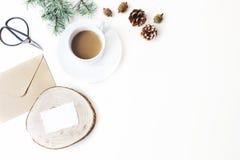 De samenstelling van de Kerstmiskantoorbehoeften Kop van koffie, denneappels, Kerstboomtakken en uitstekende schaar Witte lijst royalty-vrije stock afbeelding