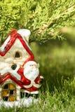 De Samenstelling van de nieuwjaarwinter Kerstman` s huis, stuk speelgoed Kerstman onder de boom Royalty-vrije Stock Afbeelding