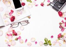 De samenstelling van rode rozen, bloemblaadjes, tijdschrift, telefoon, camera Royalty-vrije Stock Foto