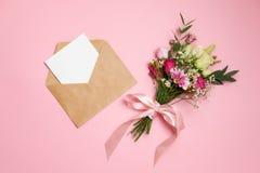 De samenstelling van de valentijnskaartendag: het boeket van bloemen, kraftpapier-envelop met groetkaart legt bij roze achtergron stock afbeelding