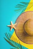 De samenstelling van de zomer Tropische palmbladen, de hoed van het strostrand, zeester op pastelkleur blauwe en gele achtergrond Royalty-vrije Stock Fotografie