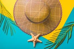 De samenstelling van de zomer Tropische palmbladen, de hoed van het strostrand, zeester op pastelkleur blauwe en gele achtergrond Stock Foto's