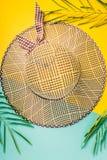 De samenstelling van de zomer Tropische palmbladen, de hoed van het strostrand, zeester op pastelkleur blauwe en gele achtergrond Stock Afbeeldingen
