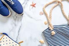 De samenstelling van de de zomervakantie Modieuze blauwe tennisschoenen, gestreepte strandzak, zeeschelpen, overzeese ster op mar stock fotografie