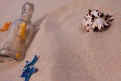 De samenstellingen van het strand. Botlle die door het water wordt gebracht Stock Foto