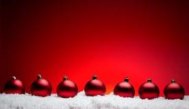 De samenstellingsballen van het Kerstmis nieuwe jaar met rode backgro van de sneeuwlijn Stock Afbeeldingen