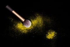 De samenstellingsborstel met geel gemorst poeder schittert stof op zwarte achtergrond Make-upborstel op nieuwe jaar` s Partij met stock afbeelding