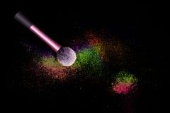 De samenstellingsborstel met kleurrijk gemorst poeder schittert stof op zwarte achtergrond Make-upborstel op nieuwe jaar` s Parti stock foto