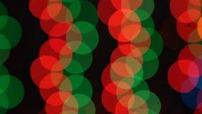 De samenvatting defocused kleurrijke het knipperen lichten Kerstmis en Nieuwjaarslinger op een zwarte achtergrond Naadloze loopab stock videobeelden