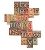 De samenvatting van het alfabet in houten doopvonten Stock Afbeelding
