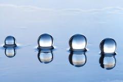 De samenvatting van waterparels met bezinning over donkere oppervlakte Stock Afbeeldingen