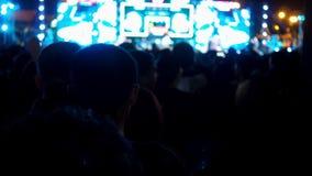 De samenvatting vertroebelde menigtemensen die in de muziekfestival van het muziekoverleg genieten van stock videobeelden