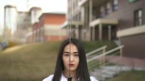 De samoerai bekijkt blad van haar naakt zwaard De wind blaast het haar van het meisje Het meisje is kalm stock footage
